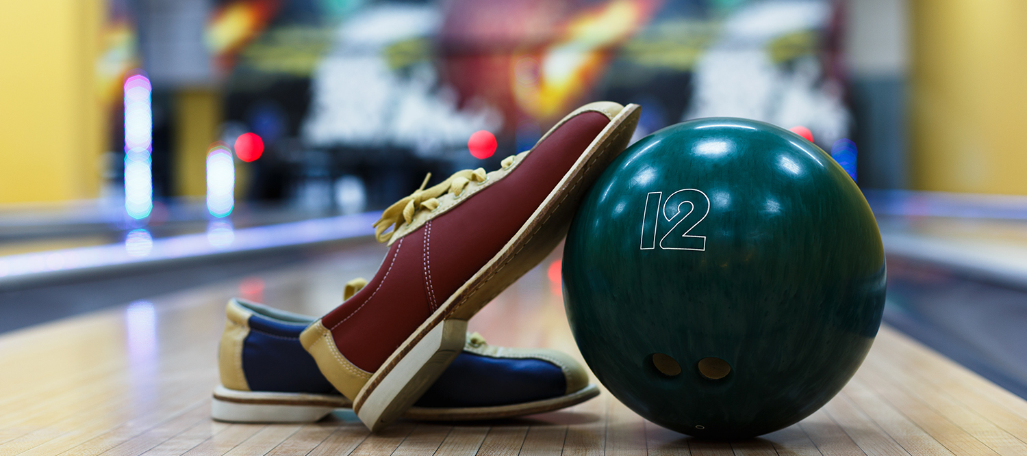 Image of bowling shoes and bowling ball on bowling alley.