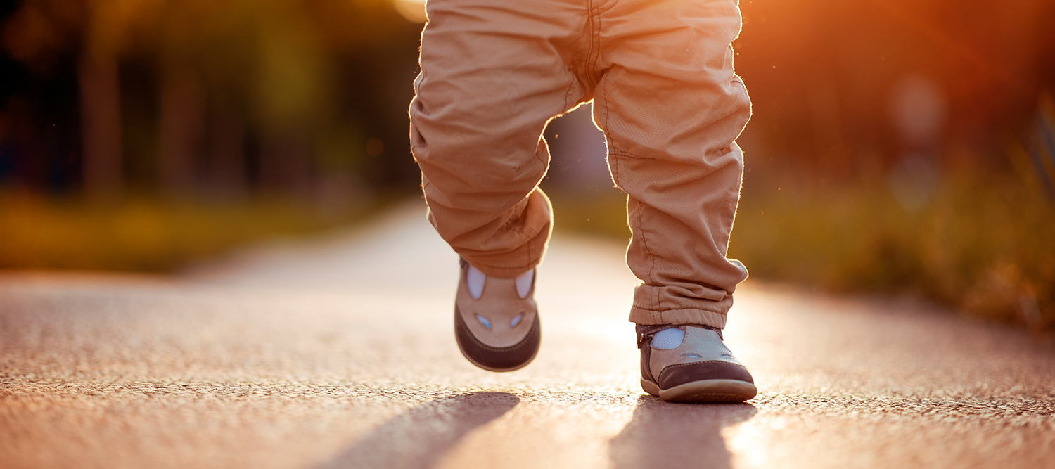 toddler legs walking on sidewalk