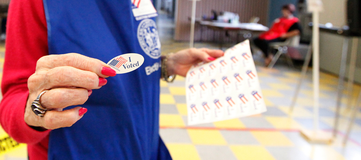 "Image of attendant handing out an ""I voted"" sticker."