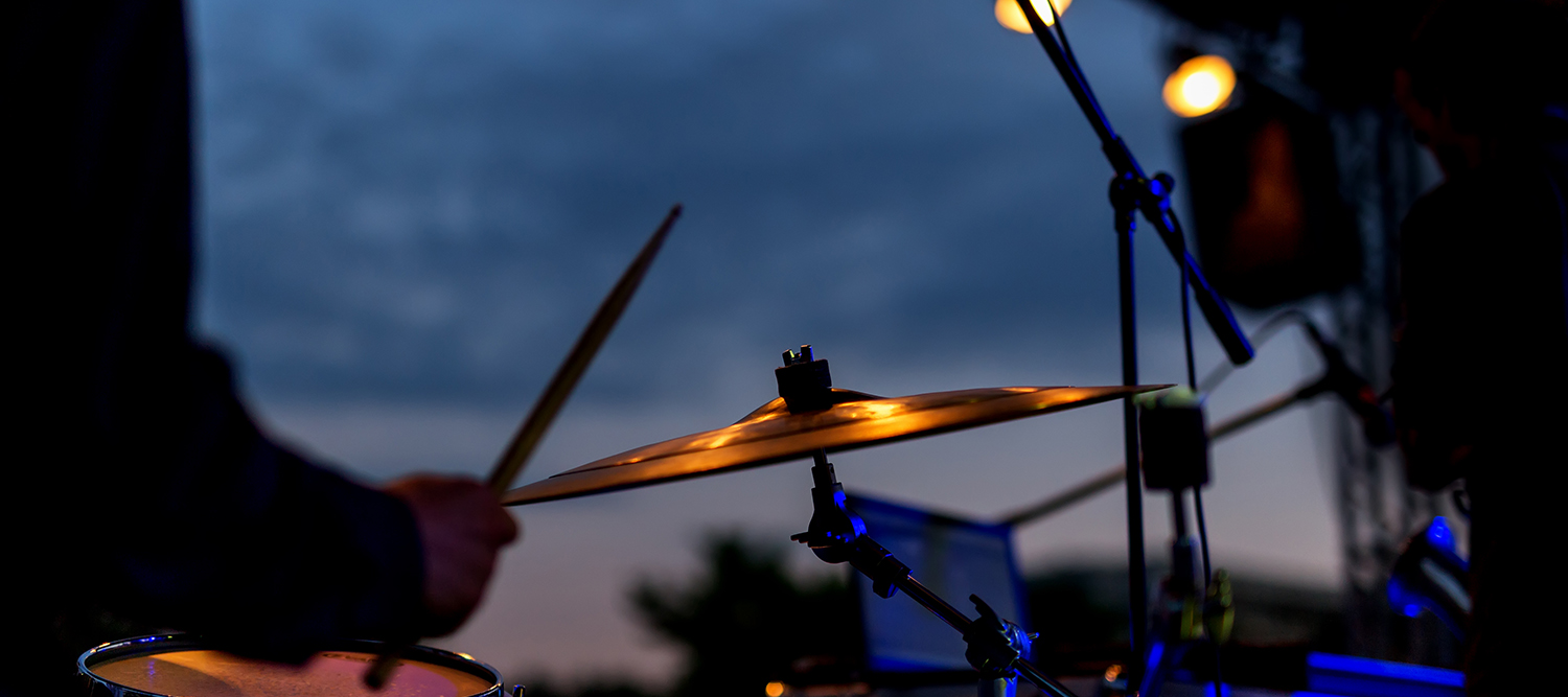 photo of a man on stage playing the drums in the evening.