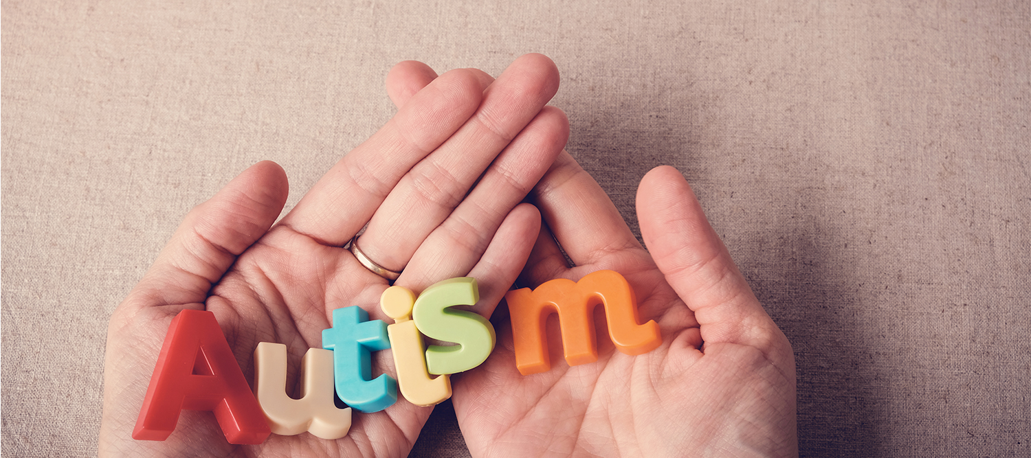 hands holding colorful letters that spell out Autism.