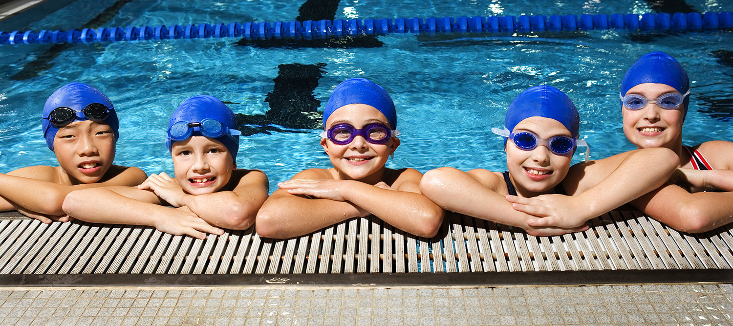 Picture of children in a pool leaning on the cement, wearing swim caps and goggles.
