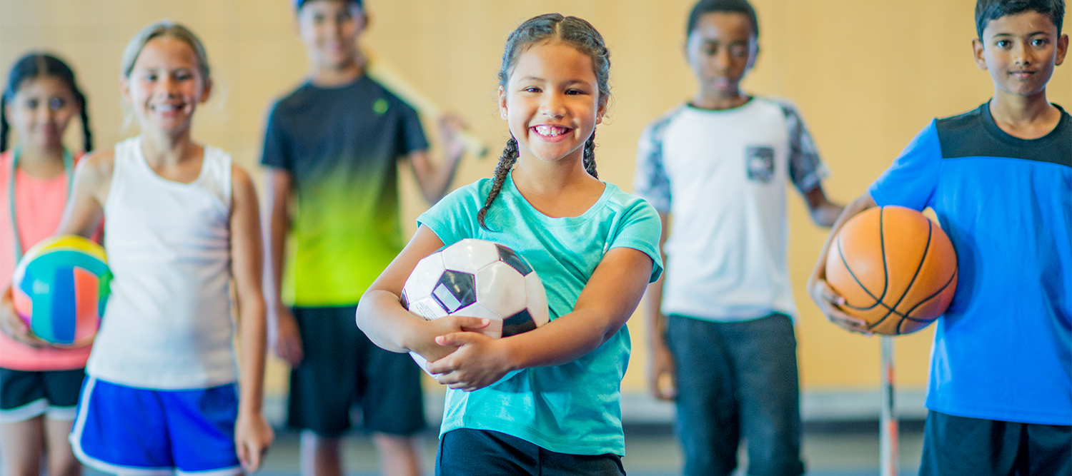 Children holding sports balls (soccer ball, basketball, volleyball)