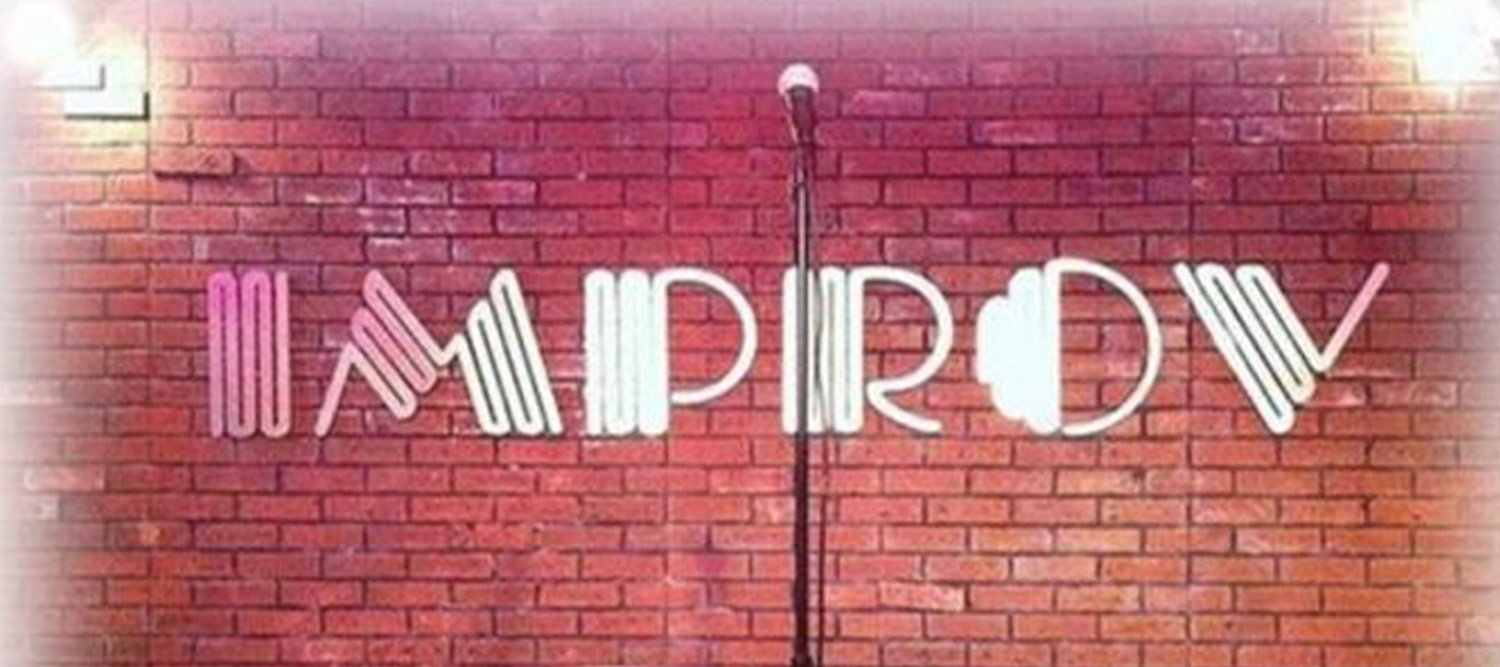 "photo of a brick wall with a microphone in front and the word ""Improv"" across the image."