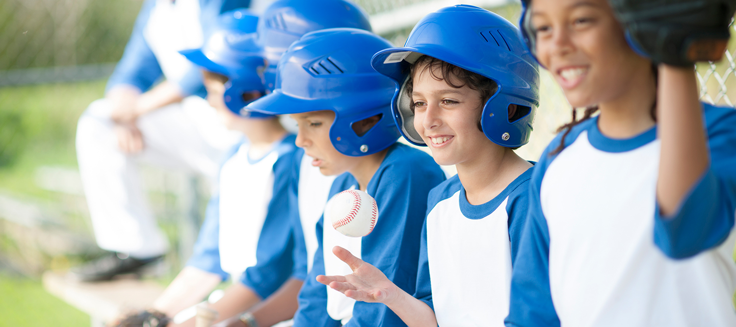 photo of children in blue and white baseball uniforms sitting in a dug out.