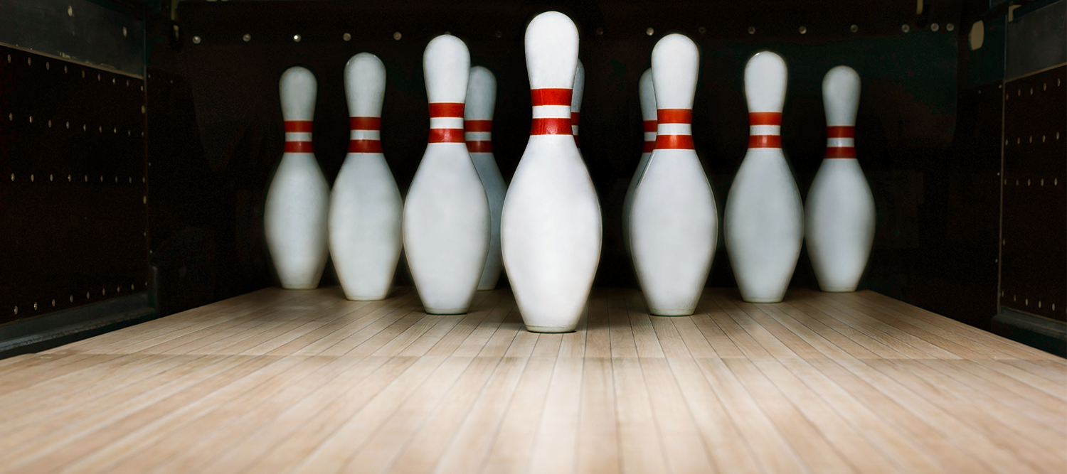 photo of bowling pins set up in a bowling lane.