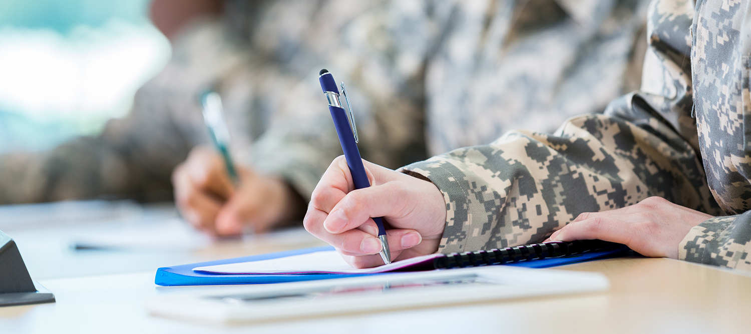 Photo of military student in uniform and taking notes at a desk.