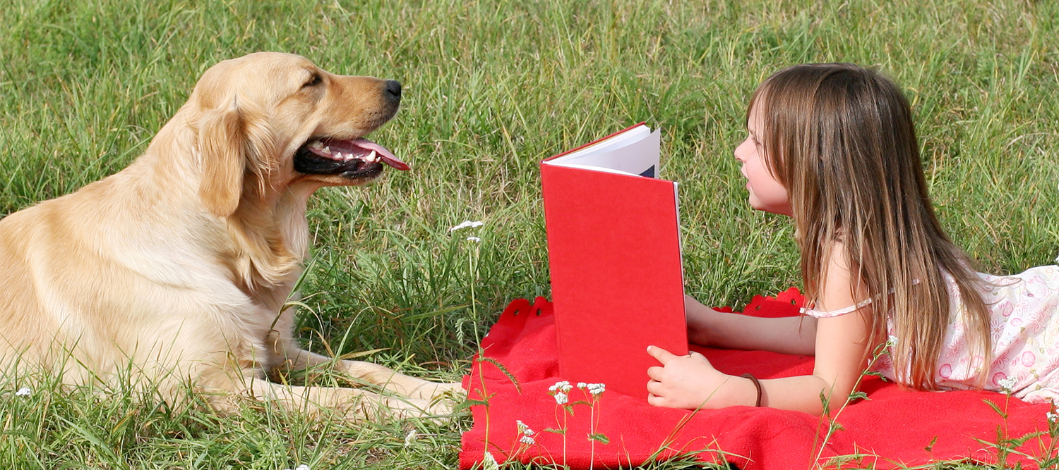 Photo of girl reading to a dog in a park.